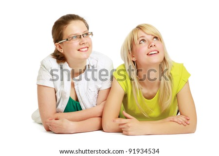 Smilimg girls lying on floor and looking up, isolated on white background