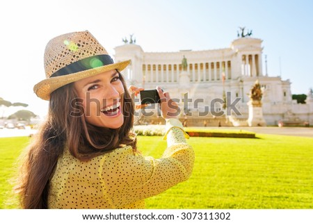 Smiling, a woman tourist takes a photo of the Venice Square monument in the distance on a summer's day in Rome. - stock photo