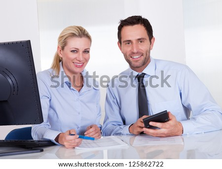 Smiling accountants discussing reports at the office - stock photo
