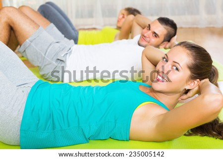 Smiling active people working out on mats in gym - stock photo