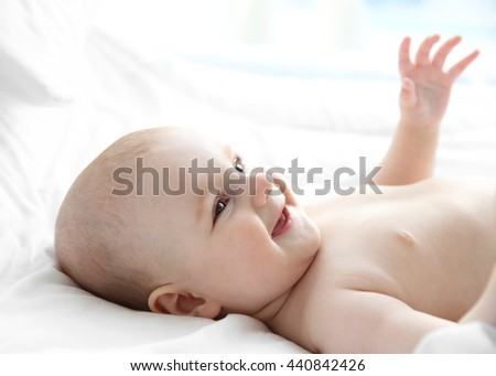 Smiling adorable baby on white bed - stock photo