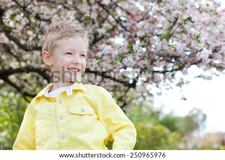 smiling adorable boy at spring time with blooming tree in the background - stock photo