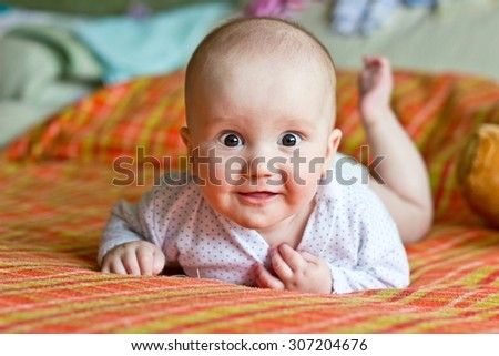 Smiling adorable little boy portrait. Lying on bed and looking at camera - stock photo