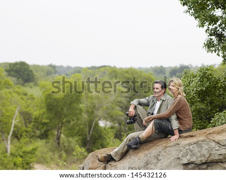 Smiling adult couple sitting on rock and enjoying the view - stock photo