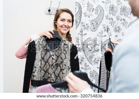 Smiling adult couple standing at boutique changing cubicle - stock photo