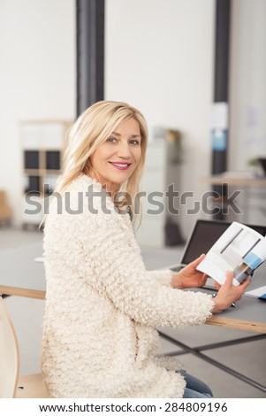 Smiling Adult Office Woman in Furry Off-White Coat, Sitting at her Desk While Holding a Book and Looking at the Camera. - stock photo