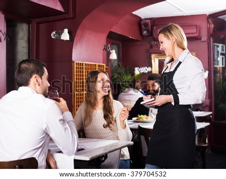 Smiling adult spouses having date in middle class restaurant. Focus on blonde girl - stock photo