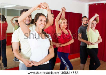 Smiling adults dancing the bachata together in a dance studio  - stock photo
