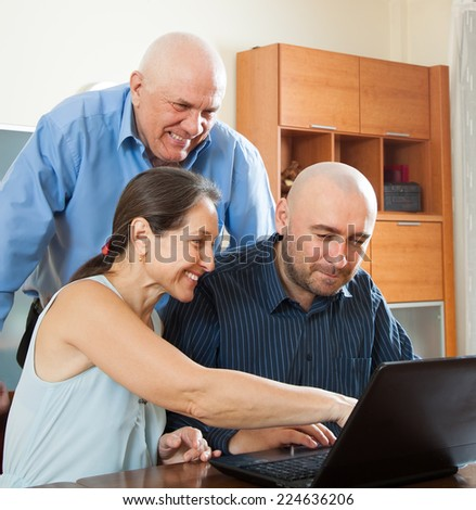 Smiling advisor   near mature couple with laptop