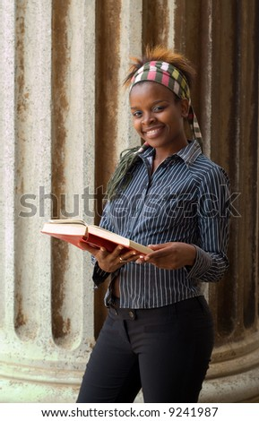Smiling African American college student reading book in front of classical library pillar - stock photo