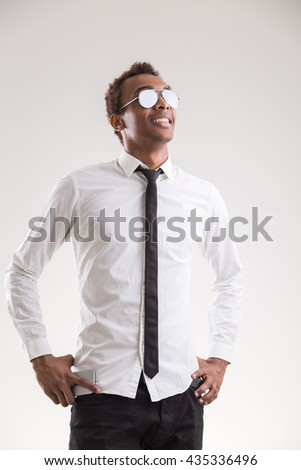 Smiling african american guy in sunglasses and formal outfit on light background - stock photo