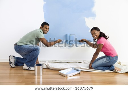 Smiling African American male and female couple painting wall blue. - stock photo