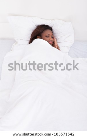 Smiling African American woman sleeping in bed