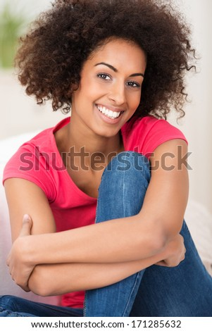 Smiling African American woman with an Afro hairstyle sitting hugging her knee and beaming at the camera