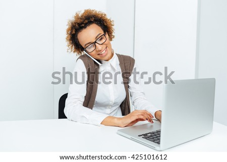 Smiling african american young business woman using laptop and talking on cell phone in office