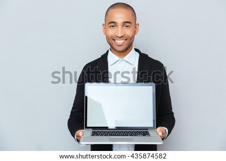 Smiling african american young man holding blank screen laptop