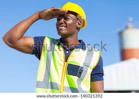 smiling african builder looking into distance - stock photo