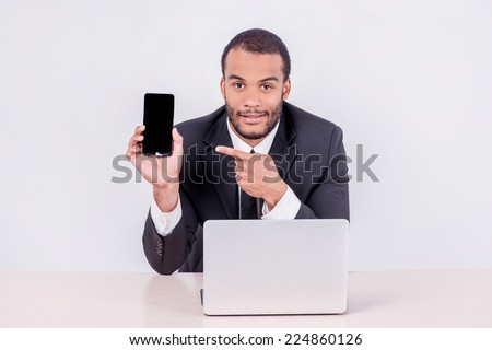 Smiling African businessman sitting at the table and pointing at a mobile phone while businessman sitting at the table and working on a laptop isolated on a gray background - stock photo