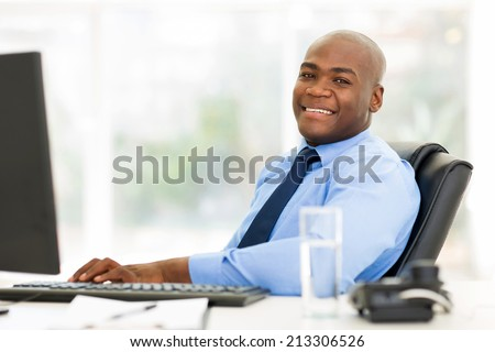 smiling african businessman sitting in office looking at the camera - stock photo