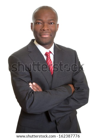 Smiling african businessman with crossed arms in black suit - stock photo