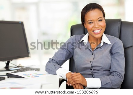 smiling african businesswoman sitting in office looking at the camera - stock photo