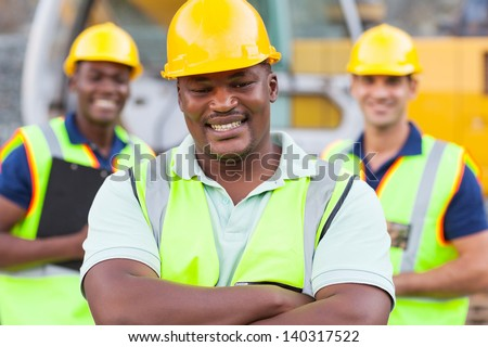 smiling african construction worker with colleagues - stock photo