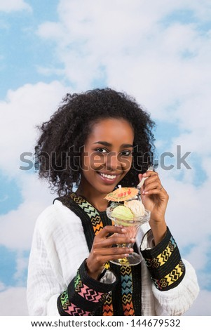 Smiling African girl with Ethiopian costume eating icecream - stock photo