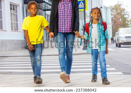 Smiling African kids with woman safely walking over the crossing on the street holding grown-up's hands after crossing the cross road of the city - stock photo