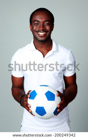 Smiling african man holding soccer ball on gray background