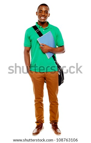 Smiling african student carrying laptop bag and notebook, full length portrait
