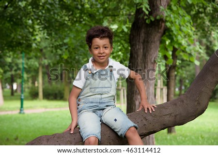 smiling afro-american boy seven years old in denim overall sit on a tree trunk