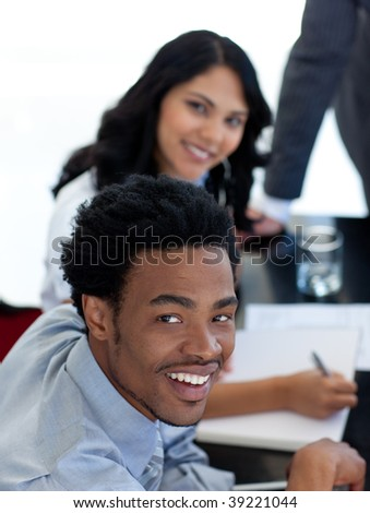 Smiling Afro-American businessman in a meeting with his colleagues - stock photo