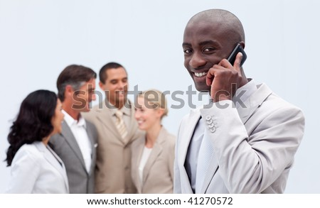 Smiling Afro-American businessman on phone at workplace with his colleagues in the background - stock photo