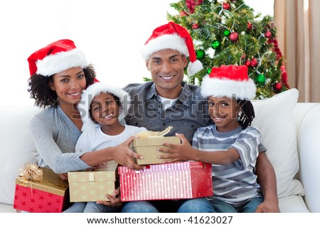 Smiling Afro-American family sharing Christmas presents on the sofa