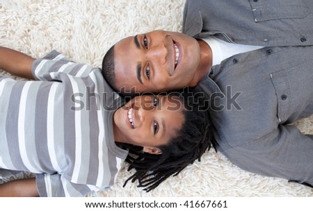 Smiling Afro-American Father and his son on floor with heads together - stock photo