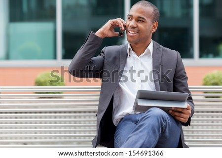 Smiling afro american manager sitting on a bench and phoning - stock photo