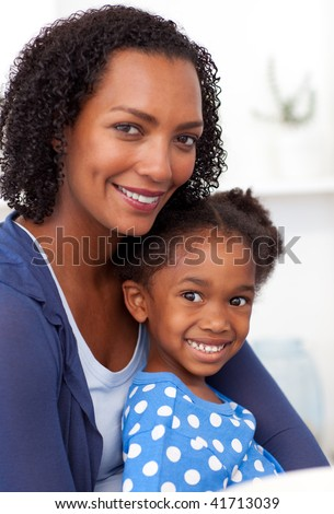 Smiling Afro-american mother and her little girl at home - stock photo