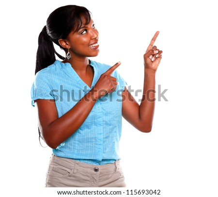 Smiling afro-american woman pointing and looking up against white background - copyspace - stock photo