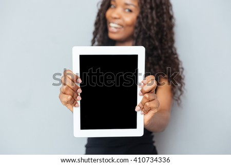 Smiling afro american woman showing blank tablet computer over gray background. Focus on tablet computer - stock photo