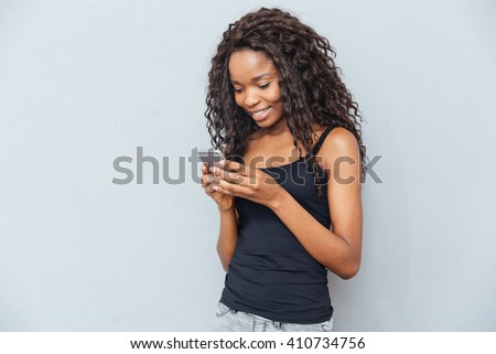 Smiling afro american woman using smartphone over gray background - stock photo