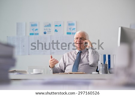 Smiling aged businessman talking on the phone in his office