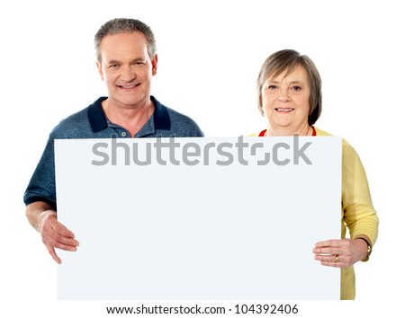 Smiling aged couple holding blank white poster showing it to camera - stock photo