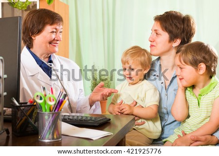 Smiling aged female pediatrician doctor examining two kids in clinic