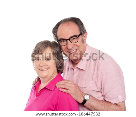 Smiling aged love couple posing as man rests his hands on woman's shoulders