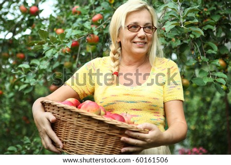 Smiling aged woman holding a basket with apples