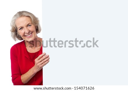 Smiling aged woman with an advertising board - stock photo