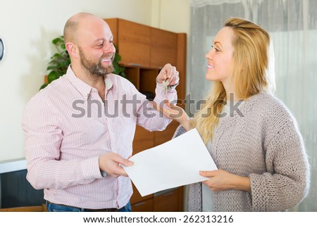 Smiling agent giving to happy female client keys from flat and papers - stock photo