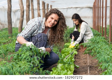 Smiling agriculture woman worker in front and colleague in back - stock photo