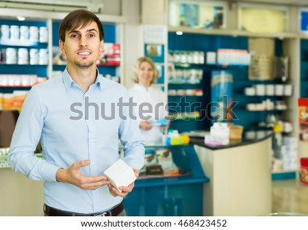smiling american handsome man   in pharmacy drugstore