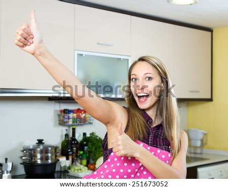 Smiling american woman in kitchen giving thumbs up